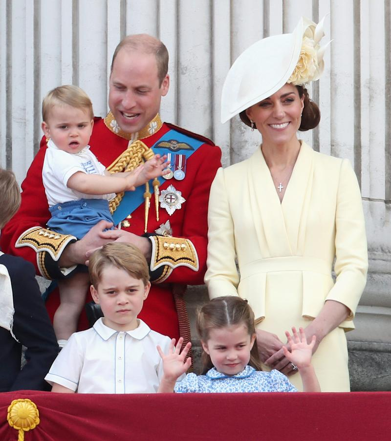Prince William, Duchess Kate of Cambridge, Prince Louis, Prince George and Princess Charlotte on the balcony at Buckingham Palace at the end of the Trooping the Colour parade on June 8, 2019 in London. Kate is wearing a dress by Alexander McQueen in warm yellow with a Philip Treacy hat.