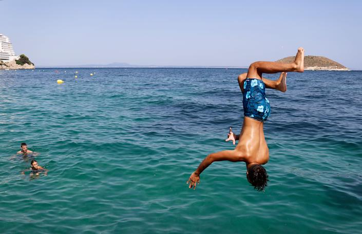 A boy jumps into the sea from the rocks of Magaluf beach on July 30 in Mallorca, Spain. The area is a popular tourist destination, particularly for British travelers. (Photo: Clara Margais via Getty Images)