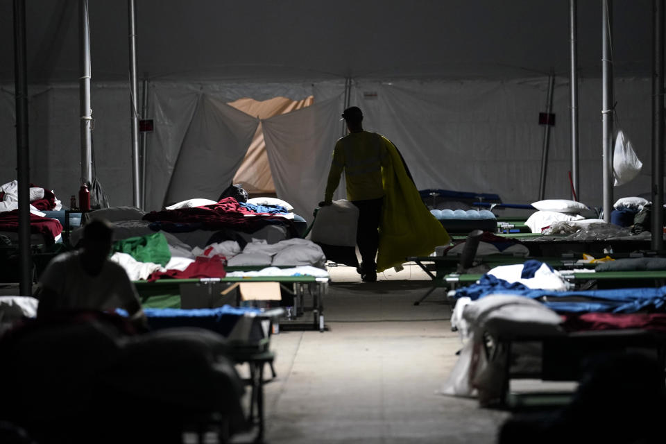 Electrical workers make their beds in a tent city in Amelia, La., Thursday, Sept. 16, 2021. In one massive white tent, hundreds of cots are spread out; experienced workers bring their own inflatable mattresses. Another tent houses a cafeteria that serves hot breakfast starting about 5 a.m., dinner and boxed lunches that can be eaten out in the field. (AP Photo/Gerald Herbert)