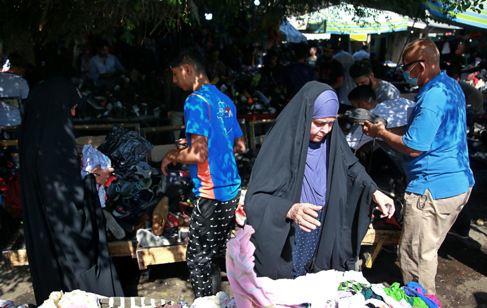 People shop for used clothes at the used-clothes market in Baghdad, Iraq, Tuesday, Oct. 20, 2020. Iraq is in the throes of an unprecedented liquidity crisis, as the cash-strapped state wrestles to pay public sector salaries and import essential goods while oil prices remain dangerously low. (AP Photo/Khalid Mohammed)