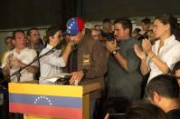 Venezuelan opposition leader Henrique Capriles, center, is surrounded by opposition leaders and supporters after he finished his speech in Caracas, Venezuela, Friday, April, 7, 2017. Capriles said today he was barred from seeking office for 15 years. The Governor of Miranda state, who came within a whisker of defeating President Nicolas Maduro in 2013 elections, is the latest in a number of prominent opposition politicians to be targeted by the embattled socialist leader's government. (AP Photo/Ariana Cubillos)