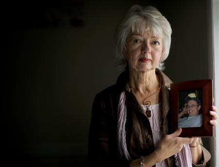 Terri Roberts, the mother of Amish school shooter Charles Roberts, holds a photograph of her son at New Covenant Community Church in Delta, Pennsylvania December 1, 2013. REUTERS/Mark Makela