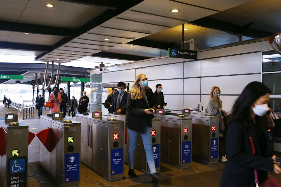 People wearing masks as they pass through Sydney transport ticket terminals.
