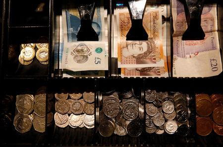 FILE PHOTO: Pound Sterling notes and change are seen inside a cash resgister in a coffee shop in Manchester, England