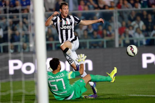 Juventus' Lichtsteiner is challenged by Atalanta's Sportiello during their Italian Serie A soccer match in Bergamo