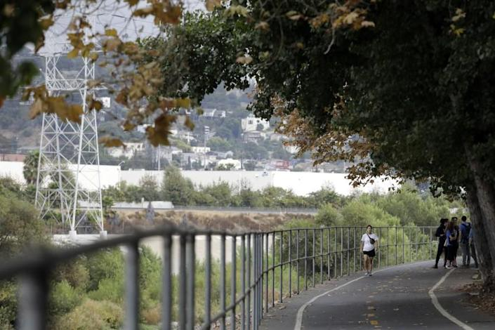 LOS ANGELES, CA -- SEPTEMBER 28, 2019: Visitors walk along the bike path across the Los Angeles River from a proposed large residential project. The land near the border of Glassell Park and Atwater Village near the Los Angeles River is the site of a proposed large residential project. There are fears it would disrupt restoration efforts, choke off access to 100 acres of public land and set a precedent for future riverside development. (Myung J. Chun / Los Angeles Times)