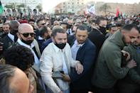Libya's newly selected Prime Minister Abdul Hamid Dbeibah (C) arrives at Martyrs' Square in the capital Tripoli to celebrate the 10th anniversary of the 2011 revolution