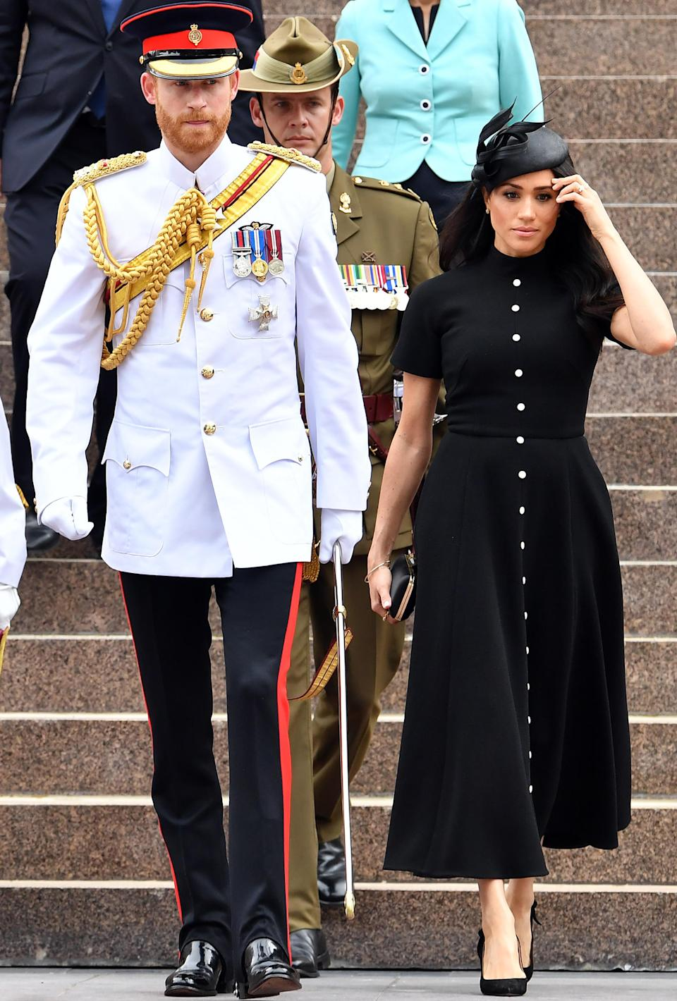 <p>At the ANZAC memorial day in Sydney, Meghan opted for Emilia Wickstead's £1,595 'Camilla' black wool crepe midi dress, with a Philip Treacy hat, a Givenchy clutch bag andTabitha Simmons slingback pumps [Photo: Getty] </p>
