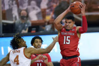 Texas Tech guard Kevin McCullar (15) grabs a rebound next to Texas forward Greg Brown (4) during the second half of an NCAA college basketball game Wednesday, Jan. 13, 2021, in Austin, Texas. (AP Photo/Eric Gay)