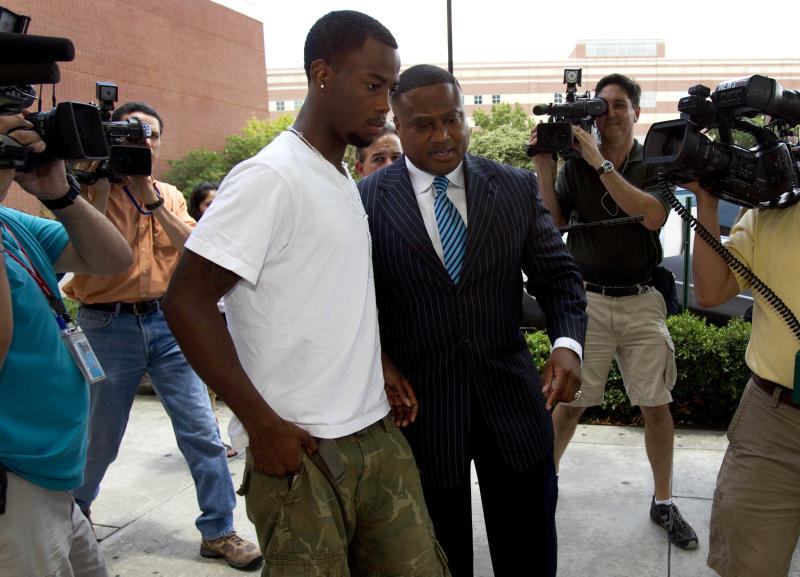 FILE - In this June 13, 2012 file photo, Chad Holley,18, center left, leaves the Harris County Jail with activist Quanell X after posting bail on a burglary charge, in Houston. Legal experts say the new arrest of Holley, who was allegedly beaten by several Houston police officers during an incident caught on video, could pose problems for prosecutors who are still trying to get convictions in the case. (AP Photo/Houston Chronicle, Brett Coomer, File)