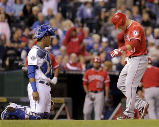 Los Angeles Angels' Mike Trout, right, crosses the plate in front of Kansas City Royals catcher Salvador Perez to score the go-ahead run after Torii Hunter was walked with the bases loaded during the eighth inning of a baseball game on Friday, Sept. 14, 2012, in Kansas City, Mo. (AP Photo/Charlie Riedel)