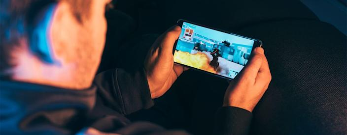 Leisure gamer plays action video game on mobile phone at night