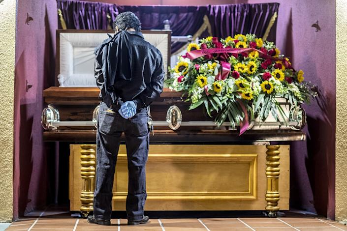 A man stands with hands clasped behind his back in front of a casket covered in sunflowers.