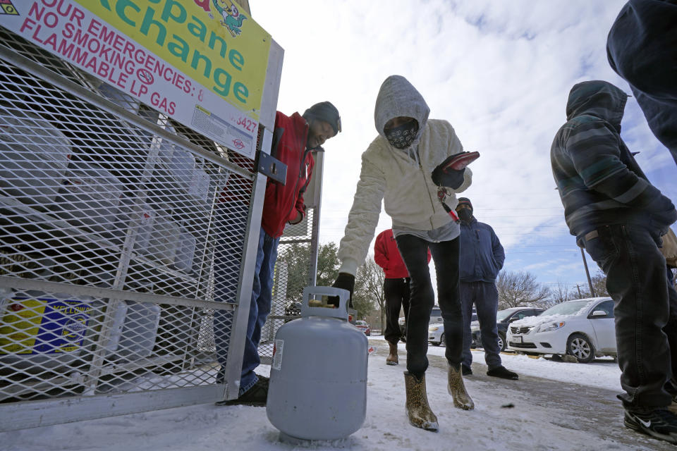 Christine Chapman, center, sets down an empty canister to exchange for a full propane tank from Robert Webster, left, outside a grocery store Tuesday, Feb. 16, 2021, in Dallas. Even though the store lost power, it was open for cash only sales. Chapman said she has been without power for two nights and is using the propane to keep warm. (AP Photo/LM Otero)