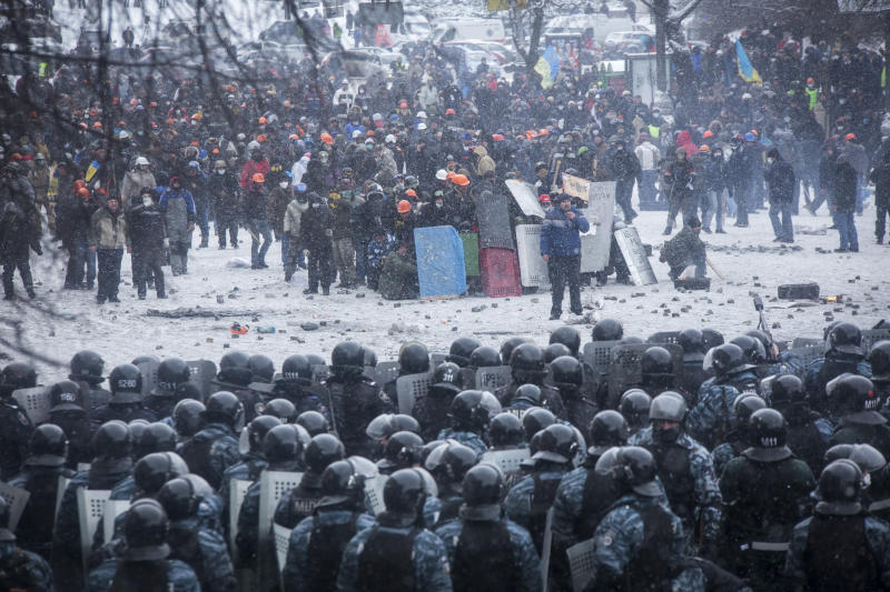 Riot police and Interior Ministry members stand in formation in front of pro-European protesters during clashes in Kiev on Jan. 22, 2014 (Stringer . / Reuters)
