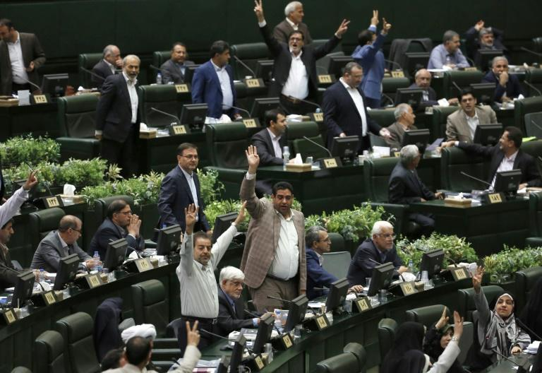 Iranian lawmakers gesture during President Hassan Rouhani's answers to the their questions in which he sought to shift the blame for the deteriorating economy to Washington even though most Iranians blame his government
