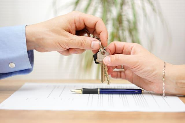 real estate agent gives house keys to his client