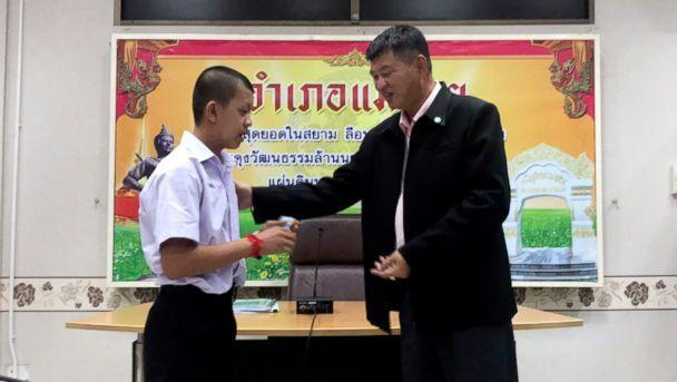 PHOTO: Pornchai Kamluang, left, receives an identity card denoting Thai citizenship from Somsak Kunkam, Sheriff of Mae Sai during a ceremony in Chiang Rai province, Thailand, Aug. 8, 2018. (Chiang Rai Public Relations Office via AP)