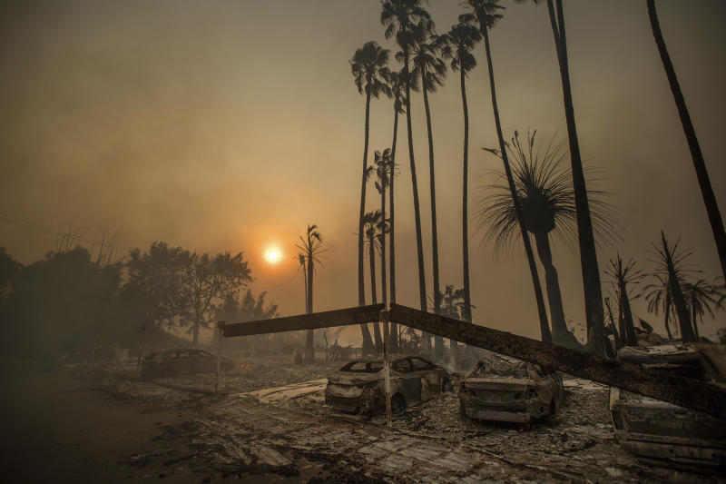 Smoke rises behind a leveled apartment complex as a wildfire burns in Ventura, Calif., on Tuesday, Dec. 5, 2017. Over 100 structures have burned so far in Ventura County, officials said. (AP Photo/Noah Berger)