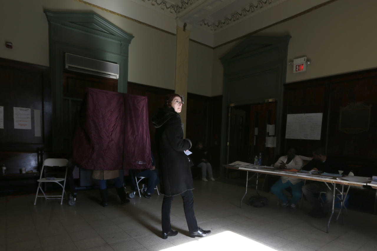 Sunlight enters through a window as a woman waits outside of a voting booth to cast her vote at Hoboken City Hall on Election Day, Tuesday, Nov. 6, 2012, in Hoboken, N.J. Voting in a the U.S. presidential election was the latest challenge for the hundreds of thousands of people in the New York-New Jersey area still affected by Superstorm Sandy, as they struggled to get to non-damaged polling places to cast their ballots in one of the tightest elections in recent history. (AP Photo/Julio Cortez)