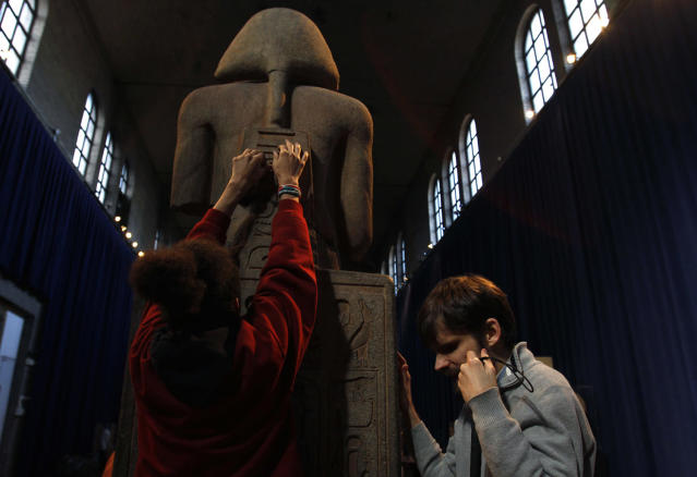 <p>Angel Ayala, left, and Austin Seraphin touch a quartzite likeness of Ramesses II at the Penn Museum in Philadelphia, Nov. 25, 2013. Ayala, 16 and blind since birth, touched ancient Egyptian artifacts at the University of Pennsylvania archaeology museum as part of a tour for the blind and visually impaired. Seraphin is also blind and helped to develop the tour. (Photo: Jacqueline Larma/AP) </p>
