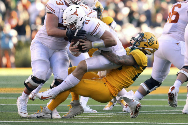 "Texas quarterback <a class=""link rapid-noclick-resp"" href=""/ncaaf/players/275098/"" data-ylk=""slk:Sam Ehlinger"">Sam Ehlinger</a> (11) is sacked by Baylor linebacker Terrel Bernard (26) in the first half of an NCAA college football game Saturday, Nov. 23, 2019, in Waco, Texas. (AP Photo/Richard W. Rodriguez)"