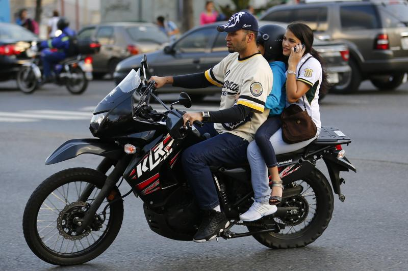 A family rides on a motorcycle among the traffic in Caracas