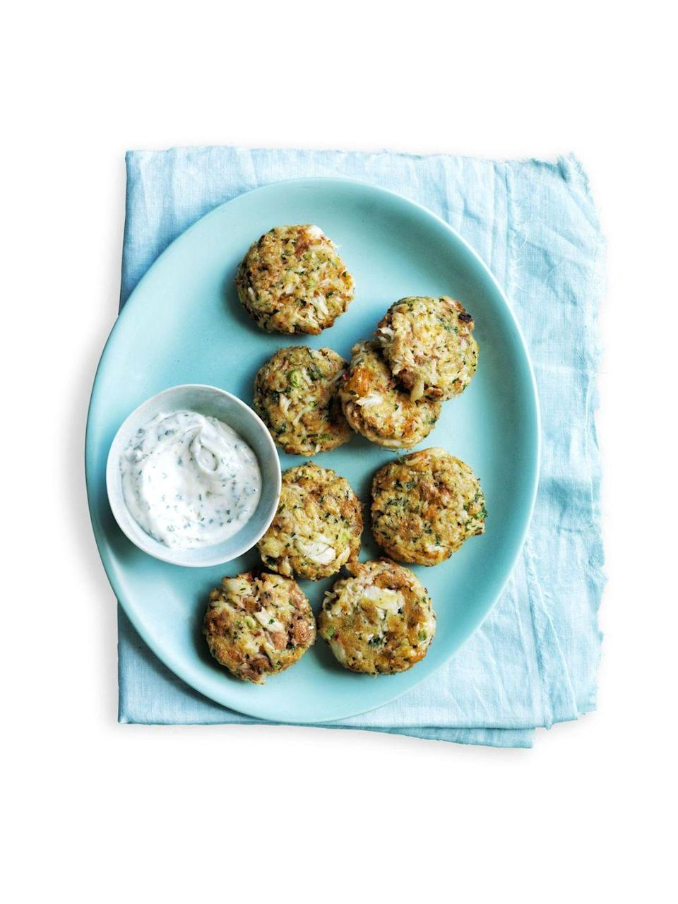 """<p>Crab cakes may seem complicated, but this straightforward recipe will have you whipping them up in no time. Throw these tangy cakes on top of some fresh greens, and you've got yourself a mighty fine dinner.</p><p><em><a href=""""https://www.womansday.com/food-recipes/food-drinks/recipes/a54836/zesty-mini-crab-cakes-recipe/"""" rel=""""nofollow noopener"""" target=""""_blank"""" data-ylk=""""slk:Get the Zesty Mini Crab Cakes recipe."""" class=""""link rapid-noclick-resp"""">Get the Zesty Mini Crab Cakes recipe.</a></em></p>"""
