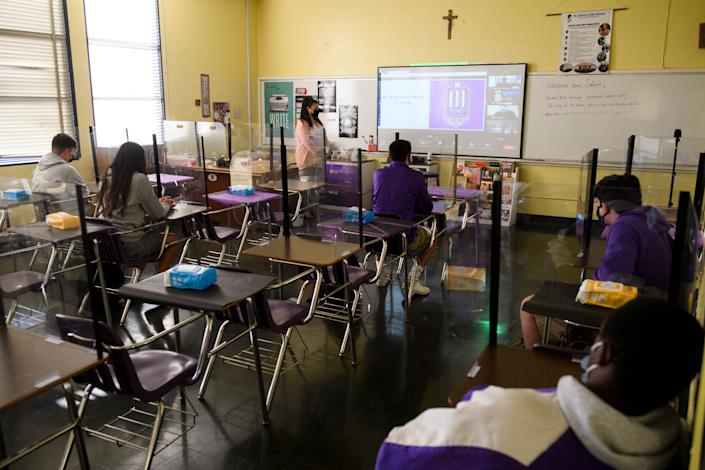 A teacher works with students both in the classroom and online at St. Anthony Catholic High School in Long Beach, Calif., on Wednesday. (Patrick T. Fallon/AFP via Getty Images)