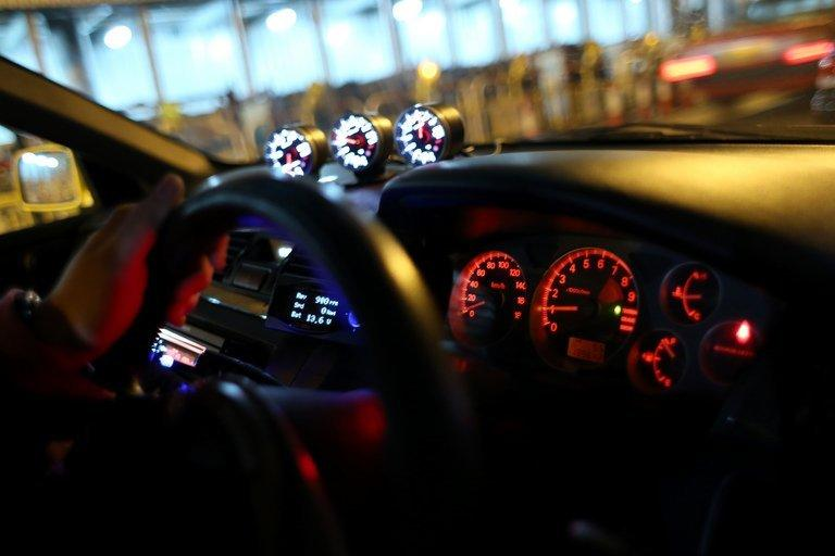 A driver places his hand on the steering wheel on his modified racing car before a race in Hong Kong, on April 7, 2013