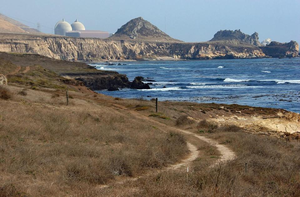 A view of a grassy dirt road, ocean, cliffs and, in the distance, reactor containment structures.