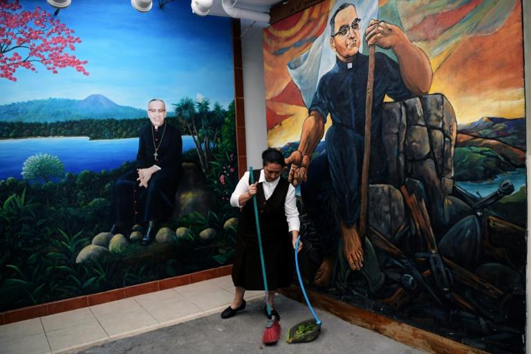 A woman sweeps near murals depicting Oscar Romero, at the Divina Providencia parish in San Salvador, on October 11, 2018