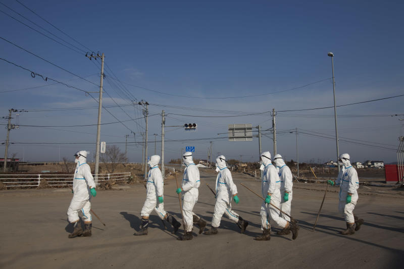 """FILE - In this April 7, 2011 file photo, Japanese police wearing protective radiation suits search for the bodies of victims of the tsunami in the Odaka area of Minami Soma, inside the deserted evacuation zone established for the 20-kilometer radius around the Fukushima Dai-ichi nuclear power plants. Japanese film director Yojyu Matsubayashi took a more standard documentary approach for his """"Fukushima: Memories of the Lost Landscape,"""" interviewing people who were displaced in the Fukushima town of Minami Soma. He followed them into temporary shelters in cluttered gymnasiums and accompanied their harried visits to abandoned homes with the gentle patience of a video-journalist. The March 2011 catastrophe in Japan has set off a flurry of independent films telling the stories of regular people who became overnight victims, stories the creators feel are being ignored by mainstream media and often silenced by the authorities. (AP Photo/David Guttenfelder, File)"""