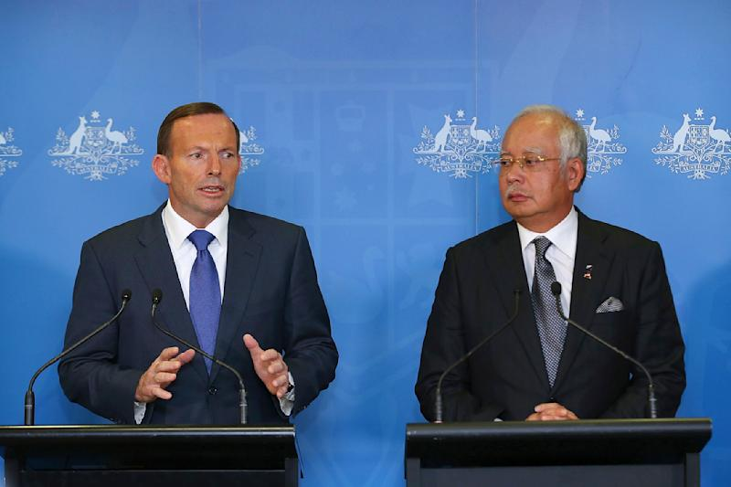FILE - In this April 3, 2014 file photo, Malaysian Prime Minister Najib Razak, right, and Australian Prime Minister Tony Abbott address the media after their meeting at the Commonwealth Parliament Offices in Perth, Australia. The leaders of Malaysia and Australia have used warm and glowing terms to assure the world that their partnership in the desperate hunt for a missing airliner is built on a firm and abiding friendship. But it's also an odd-couple relationship that has proved brittle in the past and has been blighted by hostility, rivalries and cultural misunderstandings. (AP Photo/Paul Kane, File)