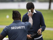 A security guard takes an attendee's temperature as a precaution against COVID-19 as they arrive at an event at Mooney's Bay Park in Ottawa, Ontario, on the Labour Day holiday weekend, Monday, Sept. 7, 2020. (Justin Tang/The Canadian Press via AP)