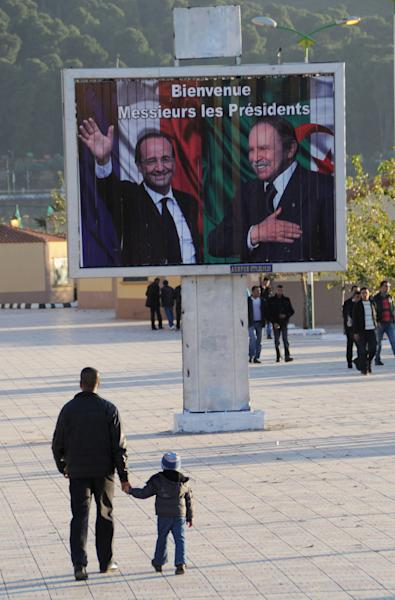 "A man and his child walk past a board reading ""Welcome Mrs Presidents"" and showing French President Francois Hollande, left, and Algerian President Abdelaziz bouteflika, Wednesday, Dec.19, 2012 in Tlemcen, northwest Algeria. Hollande is hoping for a clean start and an end to tensions with Algeria during a state visit to the country that was once the French empire's most-prized colony. The two-day state visit by the Socialist president, which begins Wednesday, comes as Algeria celebrates 50 years since its independence from France after a brutal seven-year war — and 130 years of colonial rule. Hollande will travel to Algiers and Tlemcen. (AP Photo/Nadji)"