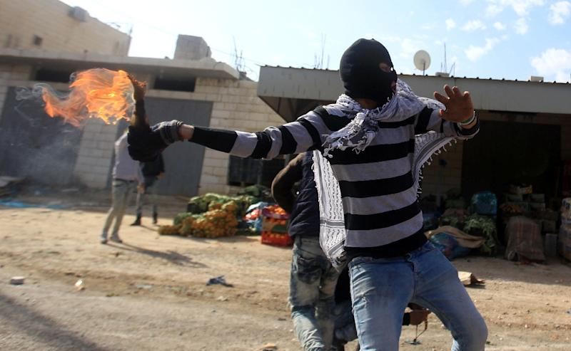 A Palestinian demonstrator throws a molotov cocktail towards Israeli security forces during clashes in the Palestinian town of Qabatiya, in the north of the Israeli-occupied West Bank, on February 5, 2016 (AFP Photo/Jaafar Ashtiyeh)