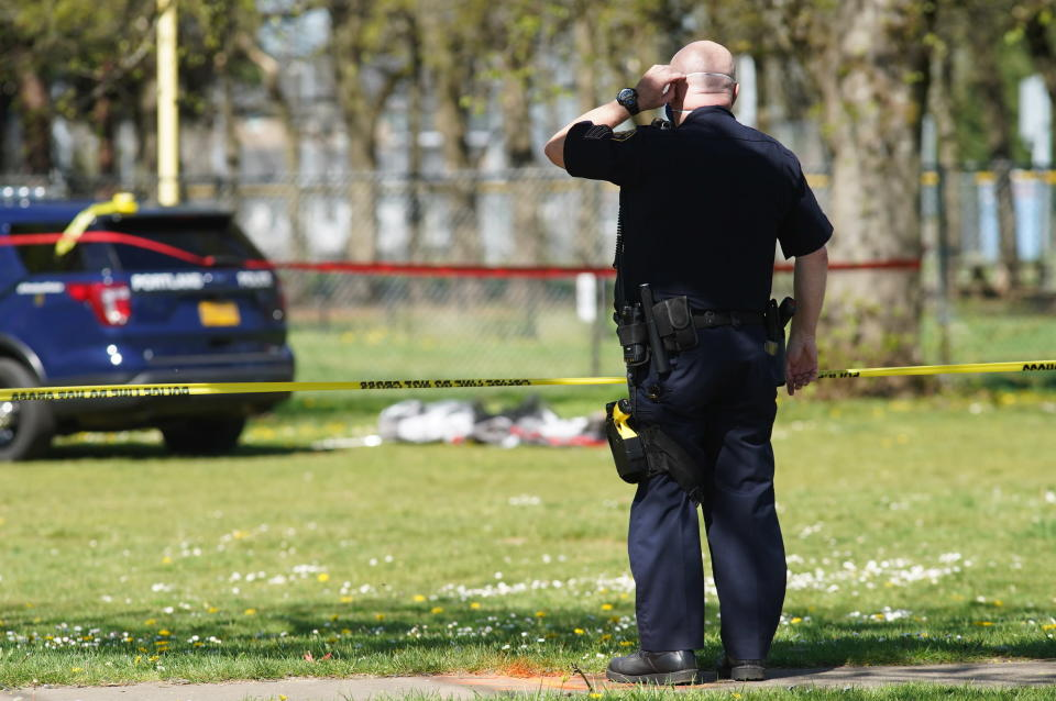 Law enforcement personnel work at the scene following a police involved shooting of a man at Lents Park, Friday, April 16, 2021, in Portland, Ore. Police fatally shot a man in the city park Friday morning after responding to reports of a person with a gun, authorities said. (Beth Nakamura/The Oregonian/The Oregonian via AP)
