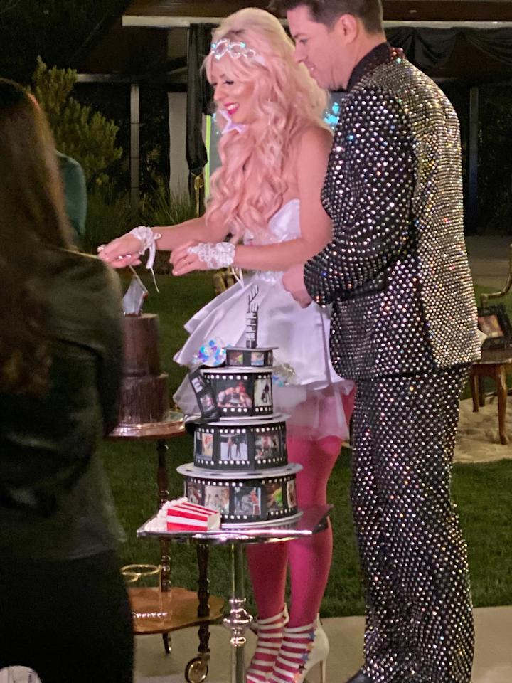 "HGTV personality <a href=""https://people.com/home/exclusive-property-brothers-j-d-scott-marries-annalee-belle-in-vintage-theatre-themed-wedding/"">J.D. Scott tied the knot with fiancee Annalee Belle</a> in a vintage movie theater-themed celebration on Halloween.  The older sibling of <a href=""https://people.com/home/drew-and-jonathan-scott-wore-mortal-kombat-costumes-to-serve-as-brother-j-d-s-groomsmen/""><em>Property Brothers'</em> Drew and Jonathan Scott</a> celebrated with 180 guests at a private residence in Las Vegas. The groom sported a rhinestone-studded suit, while his bride wore a sheer, corseted gown for the ceremony and a short ruffled dress with bright pink tights for the reception.   The couple had two wedding cakes — one covered in faux film strips featuring personal photos and a second that appears to be designed to look like wood with an axe stuck in the top."