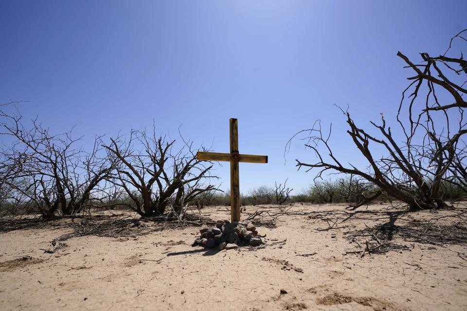 A new cross is placed by the Tucson Samaritans volunteer group at the site of the migrant who died in the desert some time ago, Tuesday, May 18, 2021, in the desert near Three Points, Ariz. (AP Photo/Ross D. Franklin)