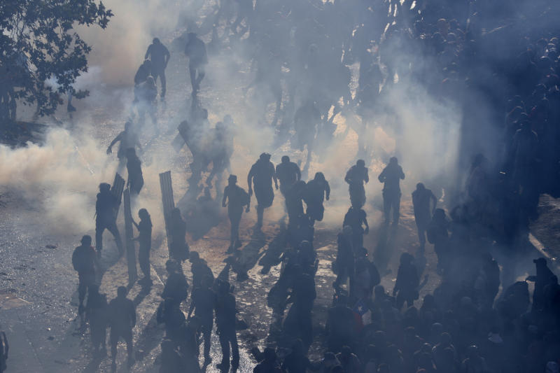 Protesters stand in tear gas launched by police amid ongoing demonstrations triggered by an increase in subway fares in Santiago, Chile, Monday, Oct. 21, 2019. (Photo: Esteban Felix/AP)