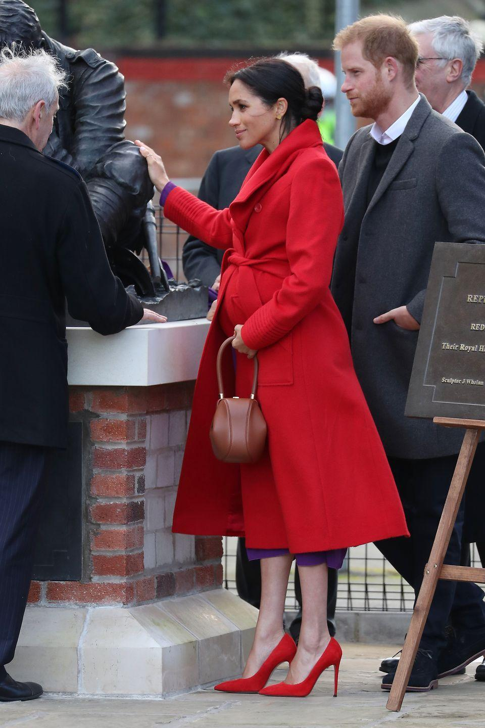 <p>The Duchess chose a bold coat with red heels for her first joint engagement with Prince Harry of the year. She paired the bright red look with matching heels and a purple dress for her day of events in Birkenhead.</p>