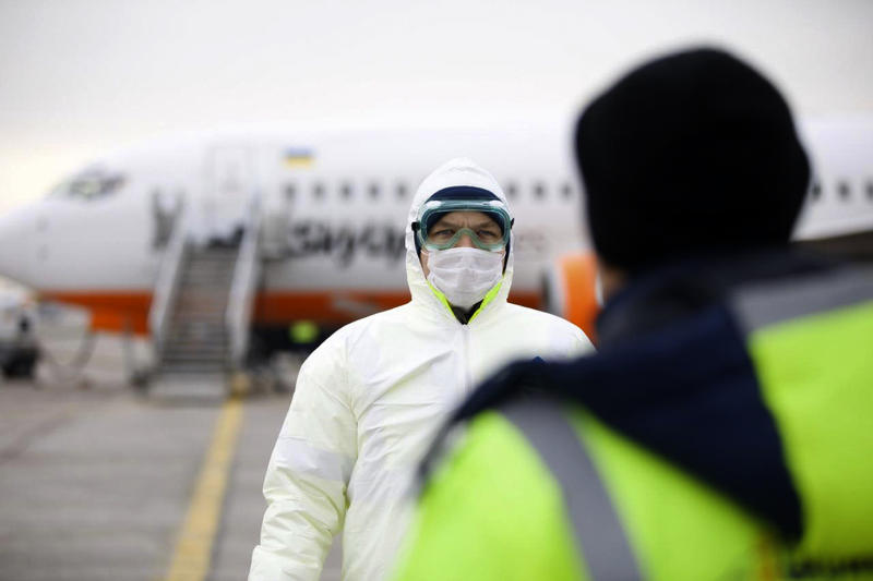 In this handout photo provided by the Ukrainian Presidential Press Office, a member of medical personnel stands ready at the Ukrainian aircraft chartered by the Ukrainian government for evacuation from the Chinese city of Wuhan, lands at Borispil international airport outside Kyiv, Ukraine, Thursday, Feb. 20, 2020. A plane carrying evacuees from Wuhan, including over 45 Ukrainians and a number of foreign passengers landed ahead of a 14-day quarantine in the country. (Ukrainian Presidential Press Office via AP)