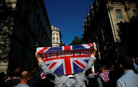 A vote leave supporter holds a Union flag, following the result of the EU referendum, outside Downing Street in London