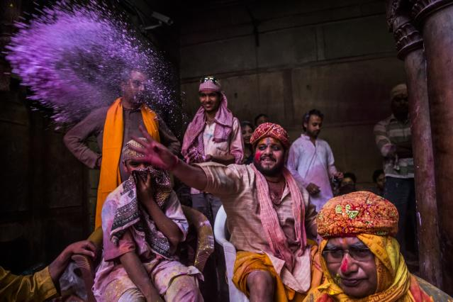 VRINDAVAN, INDIA - MARCH 26: A Hindu priest throws coloured powder at devotees during Holi celebrations, at the Banke Bihari temple on March 26, 2013 in Vrindavan, India. The tradition of playing with colours on Holi draws its roots from a legend of Radha and the Hindu God Krishna. It is believed that young Krishna was jealous of Radha's fair complexion since he himself was very dark. After questioning his mother Yashoda on the darkness of his complexion, Yashoda, teasingly asked him to colour Radha's face in which ever colour he wanted. In a mischievous mood, Krishna applied colour on Radha's face. The tradition of applying color on one's beloved is being religiously followed till date. (Photo by Daniel Berehulak/Getty Images)
