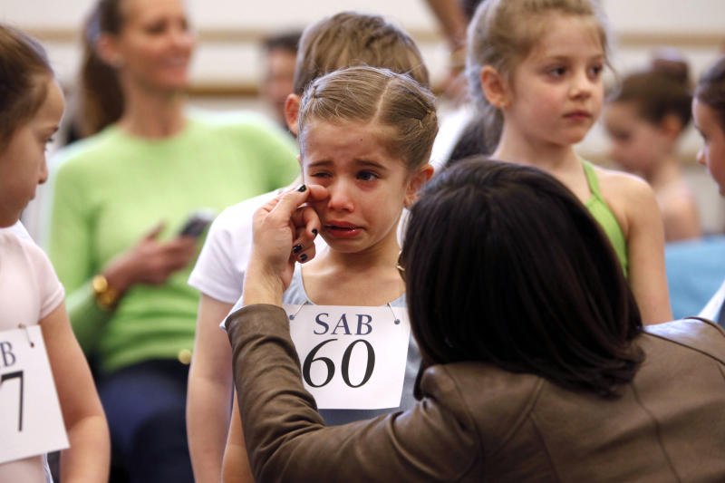 Kyra Neamonitakis, 5, of the Brooklyn borough of New York, is comforted while waiting her turn during an audition for six-year old ballet hopefuls at the School of American Ballet, Friday, April 5, 2013 in New York. (AP Photo/Jason DeCrow)