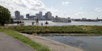 In this July 25, 2019 photo, people walk on a levee revetment in the flooded batture, bottom right, of Algiers Point on the Mississippi River in New Orleans. The river that drains much of the flood-soaked United States is running far higher than normal this hurricane season, menacing New Orleans in multiple ways. One continuing concern is the massive volume of water that for months has been pushing against levees protecting a city that's mostly below sea level. (AP Photo/Gerald Herbert)