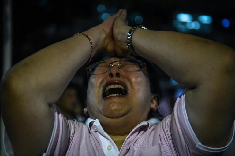 A woman reacts to the death of Thailand's King Bhumibol Adulyadej in Bangkok on October 13, 2016
