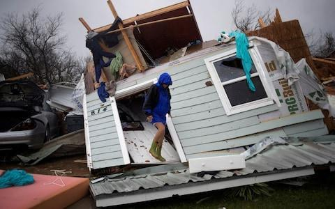<span>A woman stands on her front door as she surveys her property devastated by Hurricane Harvey in Rockport, Texas</span> <span>Credit: REUTERS/Adrees Latif </span>