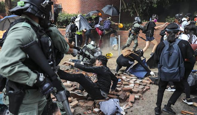 Some 19 people arrested over violent clashes near Hong Kong Polytechnic University on Sunday were charged with taking part in a riot at West Kowloon Court. Photo: Sam Tsang